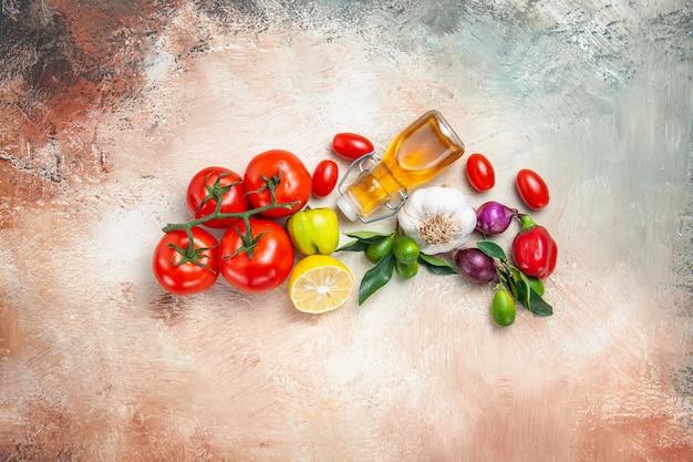 Vista superior de vegetais frutas cítricas cebola alho tomate limão com pedicelos óleo de pimenta