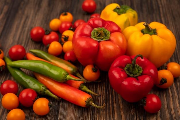 Vista superior de vegetais maduros, como tomate cereja e pimentão, isolados em uma parede de madeira