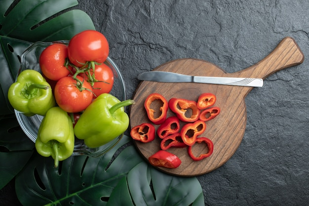 Vista superior de vegetais orgânicos frescos, fatias de pimentão vermelho na tábua de madeira e pimenta e tomate em uma tigela sobre fundo preto.