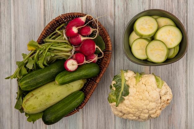 Vista superior de vegetais saudáveis, como abobrinhas de pepino e rabanetes em um balde com couve-flor isolada em um fundo cinza de madeira