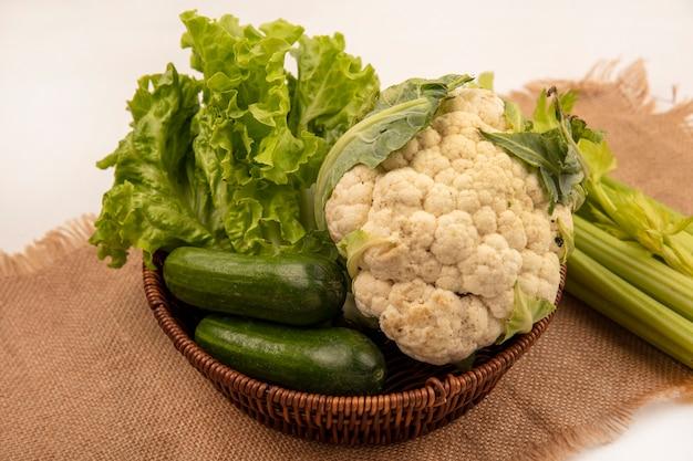Vista superior de vegetais saudáveis, como alface, couve-flor e pepino em um balde em um pano de saco com aipo isolado em uma parede branca