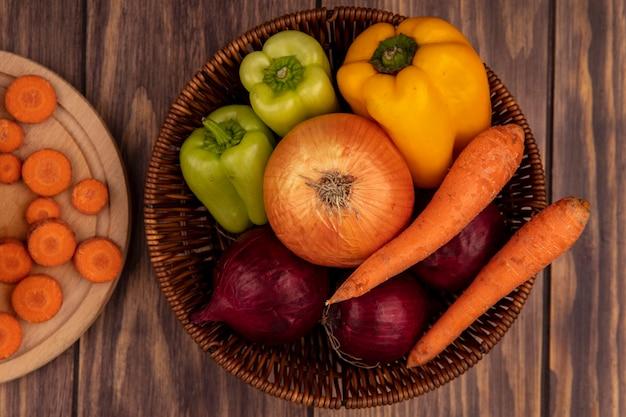 Vista superior de vegetais saudáveis, como cebolas brancas e vermelhas, pimentões coloridos e cenouras em um balde sobre uma superfície de madeira