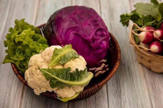 Vista superior de vegetais saudáveis, como couve-flor roxa, repolho e alface em um balde com rabanetes em um balde em uma superfície de madeira cinza