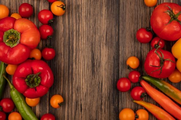 Vista superior de vegetais saudáveis, como tomates e pimentões isolados em uma parede de madeira com espaço de cópia
