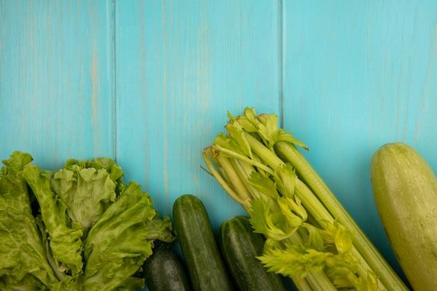 Vista superior de vegetais verdes, como abobrinhas, pepinos, alface e aipo, isolados em uma parede de madeira azul com espaço de cópia