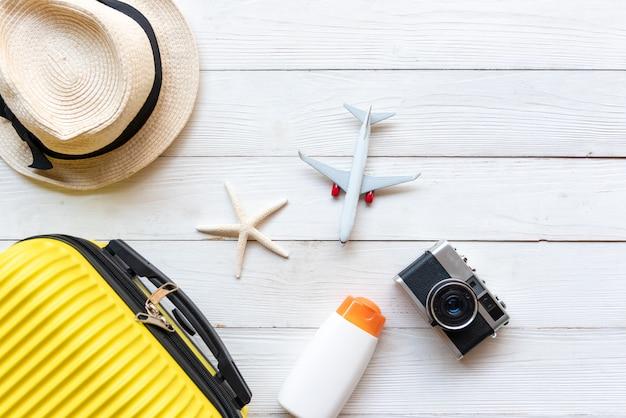 Vista superior de verão viagens e plano. bagagem mala amarela com moda acessórios, câmera antiga, protetor solar. viajar no avião de viagens de férias em madeira fundo branco em viagens de férias.