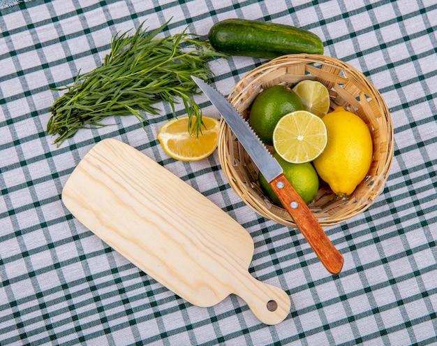 Vista superior de verduras de estragão frescas com um balde de limões e uma faca em uma toalha de mesa quadriculada
