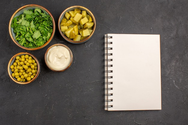 Vista superior de verduras e feijões com picles na superfície cinza