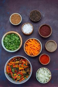 Vista superior de verduras e temperos com cebolas fatiadas e salada de legumes em mesa escura