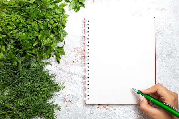 Vista superior de verduras frescas com bloco de notas na superfície branca de alimentos verdes de refeição