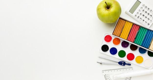 Vista superior de volta ao essencial da escola com aquarela e maçã