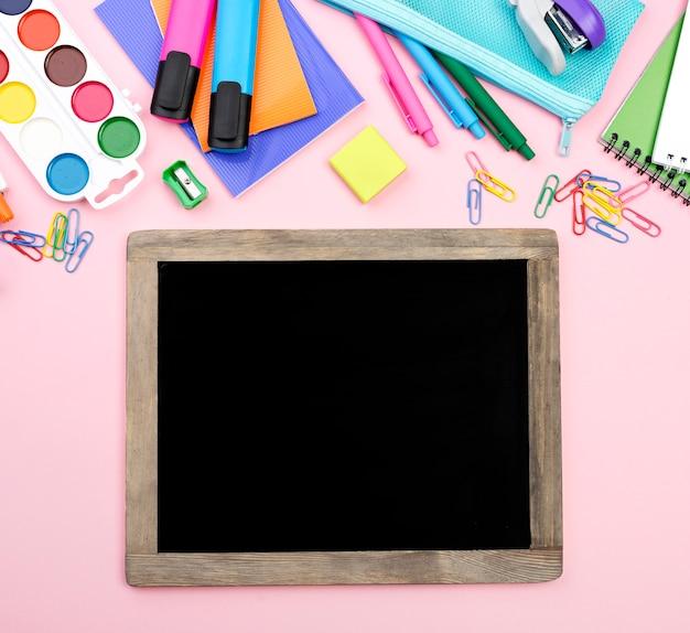 Vista superior de volta ao essencial da escola com lápis e quadro-negro