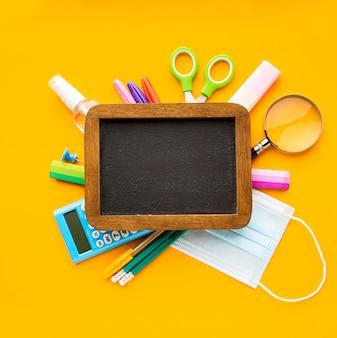 Vista superior de volta ao essencial da escola com quadro-negro e lápis