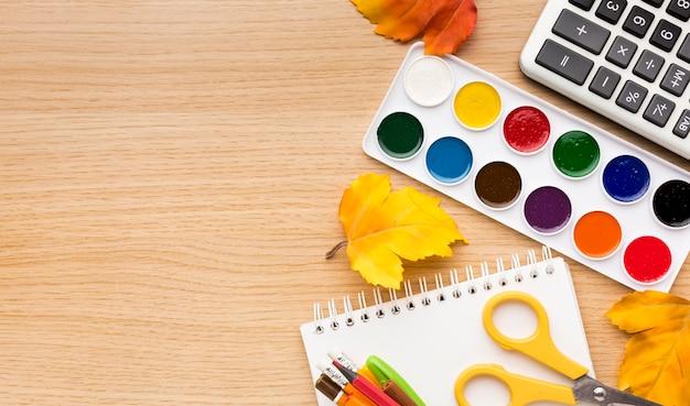 Vista superior de volta ao material escolar com caderno e aquarela