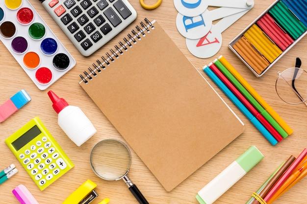 Vista superior de volta ao material escolar com lápis coloridos e caderno