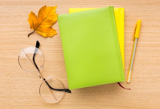 Vista superior de volta ao material escolar com livros e óculos