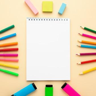 Vista superior de volta aos artigos de papelaria da escola com caderno e lápis