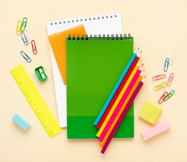 Vista superior de volta aos artigos de papelaria da escola com cadernos e lápis de cor