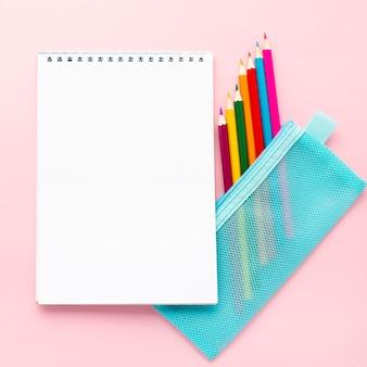 Vista superior de volta aos artigos de papelaria da escola com lápis coloridos