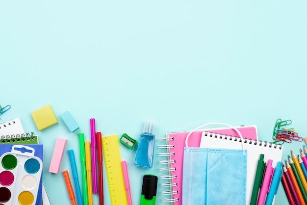 Vista superior de volta aos artigos de papelaria da escola com máscara médica e lápis coloridos