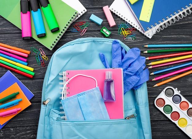 Vista superior de volta aos artigos de papelaria da escola com mochila e luvas