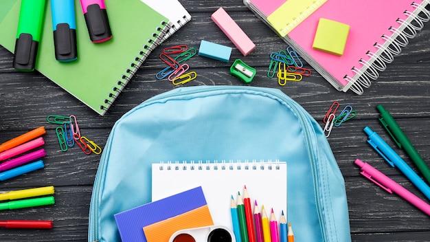 Vista superior de volta aos artigos de papelaria da escola com mochila