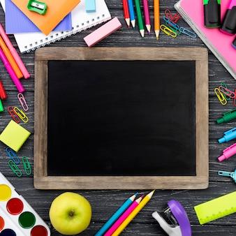 Vista superior de volta aos artigos de papelaria da escola com quadro-negro e lápis coloridos