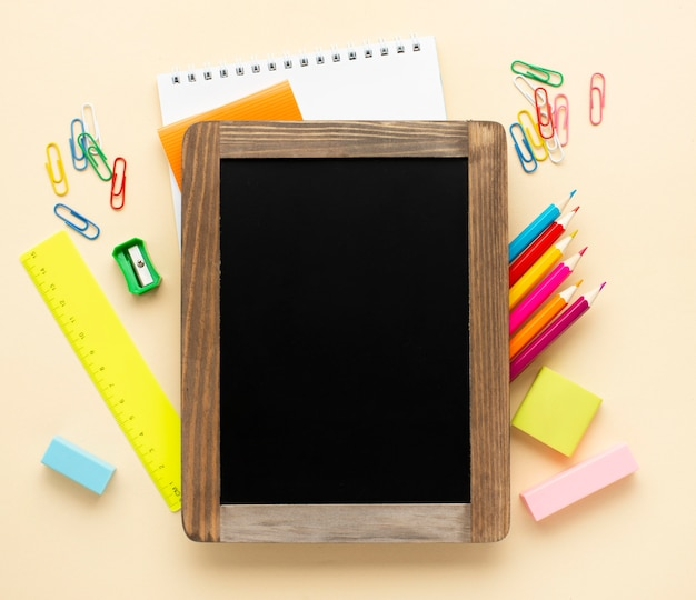 Vista superior de volta aos artigos de papelaria da escola com quadro-negro e lápis de cor