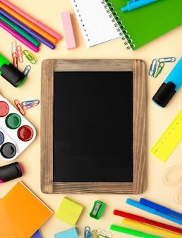 Vista superior de volta aos artigos de papelaria da escola com quadro-negro