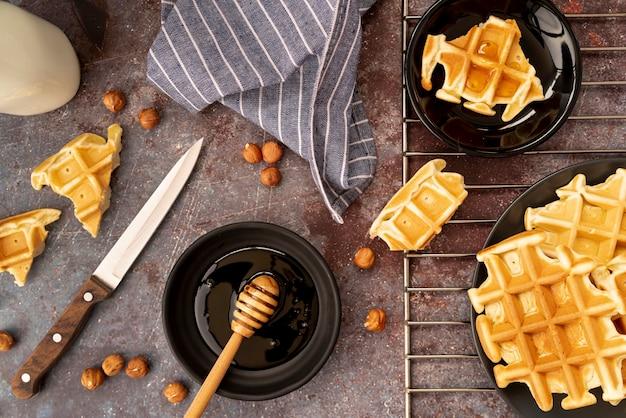 Vista superior de waffles cobertos de mel com avelãs e dipper mel