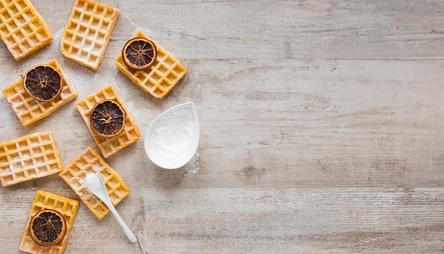 Vista superior de waffles com açúcar em pó e frutas cítricas secas