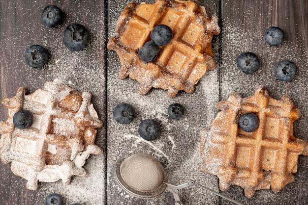 Vista superior de waffles com açúcar em pó e mirtilos