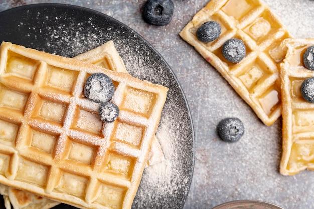 Vista superior de waffles com açúcar em pó na parte superior e mirtilos