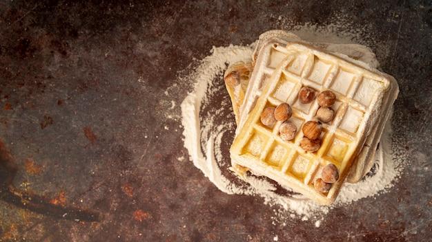 Vista superior de waffles com avelãs e açúcar em pó