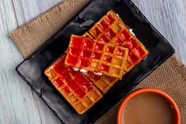 Vista superior de waffles com calda de morango e chantilly em uma bandeja preta e uma xícara de cacau