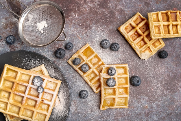 Vista superior de waffles com mirtilos e açúcar em pó