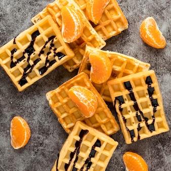 Vista superior de waffles com tangerinas e calda de chocolate