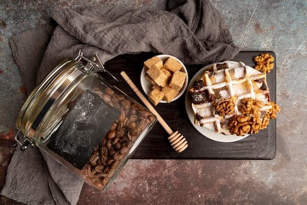 Vista superior de waffles empilhados no prato com nozes e cubos de açúcar
