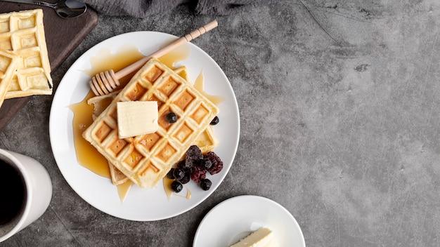 Vista superior de waffles no prato com manteiga e mel