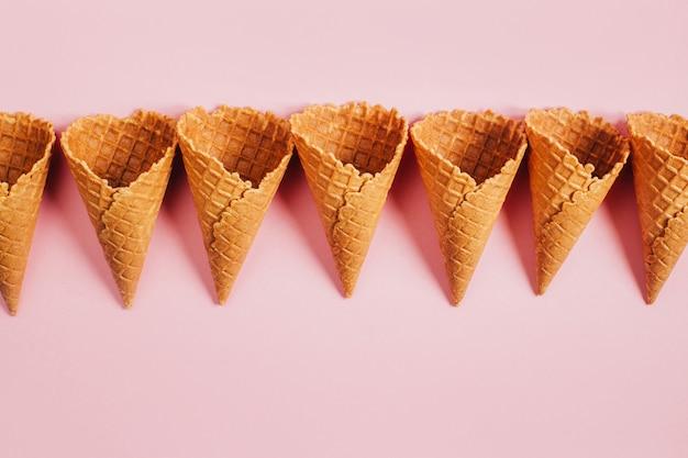 Vista superior de xícaras de sorvete waffle vazias em fundo rosa