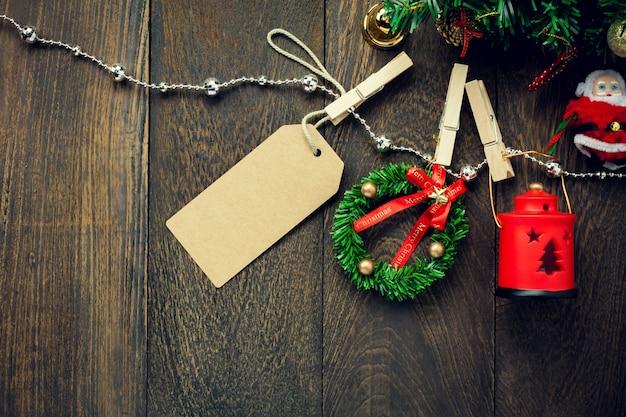 Vista superior decoração de natal, lâmpada, rótulo e corda de roupa de jóias em fundo de mesa de madeira com espaço de cópia.