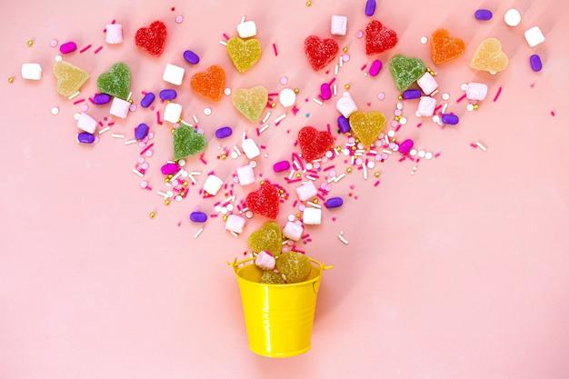 Vista superior decoração sortidas doces gomosos e geleia doces conceito feliz feriado. plano colocar doces coloridos na mesa-de-rosa linda. copie o espaço.