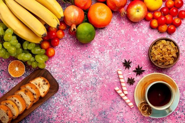 Vista superior deliciosa composição de frutas com bolos fatiados e xícara de chá na mesa rosa