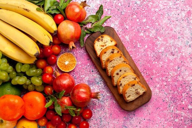 Vista superior deliciosa composição de frutas com bolos fatiados na mesa rosa claro
