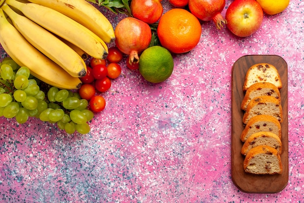 Vista superior deliciosa composição de frutas com bolos fatiados na mesa rosa