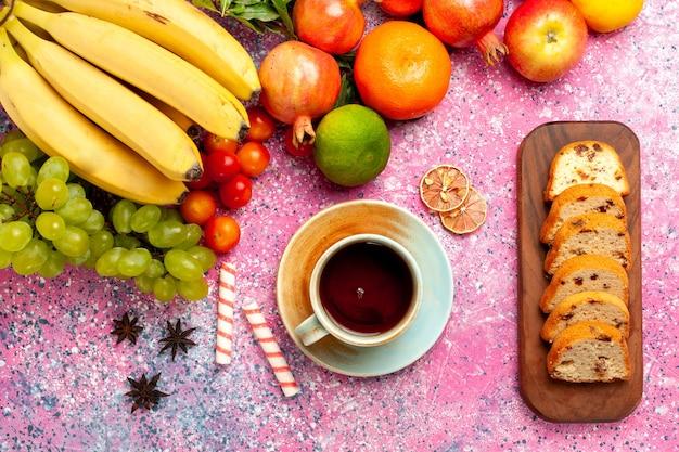 Vista superior deliciosa composição de frutas com bolos fatiados na superfície rosa
