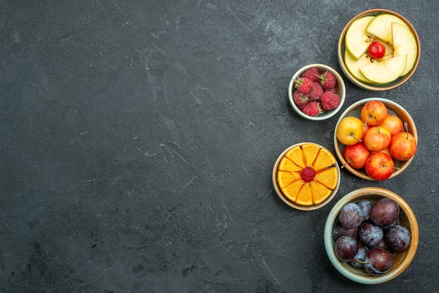 Vista superior deliciosa composição de frutas frescas fatiadas e frutas maduras em fundo escuro frutas maduras frescas dieta saudável frutas maduras