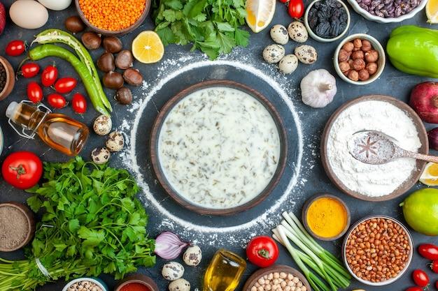 Vista superior deliciosa dovga em uma tigela de madeira coentro tomate cereja ovos de codorna farinha de alho em uma tigela de madeira pimenta na mesa
