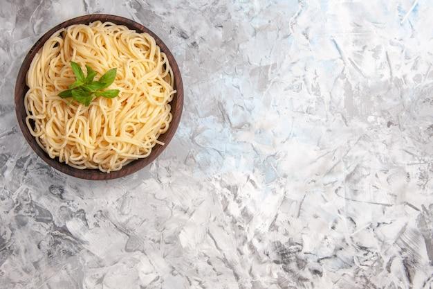 Vista superior deliciosa espaguete com folha verde na mesa branca prato massa de farinha de massa