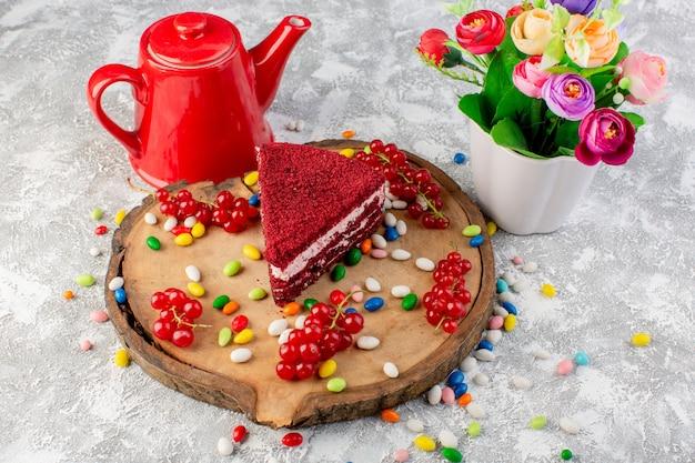Vista superior deliciosa fatia de bolo com creme e frutas junto com chaleira vermelha e flores na mesa de madeira com doces coloridos bolo biscoito chá doce